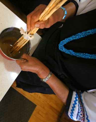 Rosie stirring her red berry mush with traditional stirring sticks. Diné girls get their stirring sticks when they become women.
