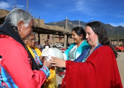 Rowen give a Taos Pueblo Squash and seeds to Taos govenor Gilbert Suazo Sr. and elder Henrietta Gomez.