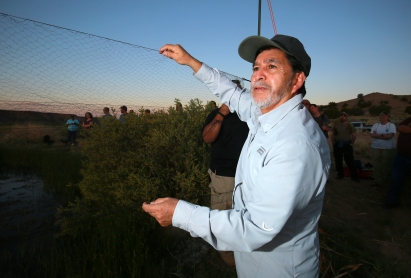 Lawrence Abeita adjusts a bat catching net above a small pond on the Sana Ana Pueblo reservation in New Mexico.