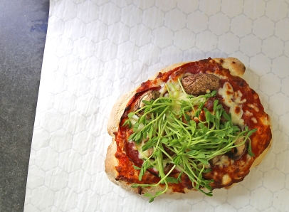 Elk sausage, mushrooms and pea shoots bannock pizza.